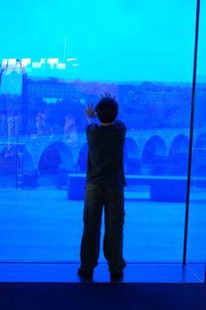 Boy looking through blue glass window onto city below.
