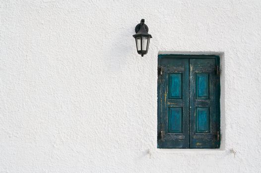 Abstract close-up of Santorini home wall, window and lamp.