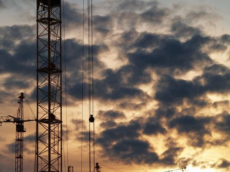Elevating cranes and sky. Sunset after rain.