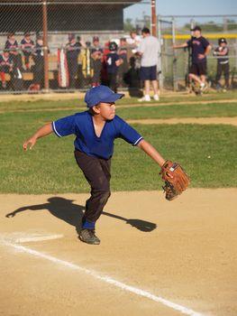 little league first baseman catching the baseball