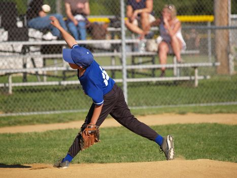 a little league baseball pitcher throwing the ball from the mound