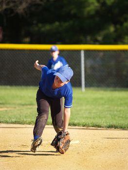 little league baseball player catching a ground ball