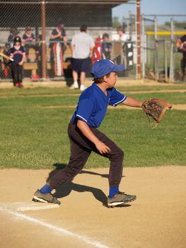 little league first baseman ball player waiting for the throw