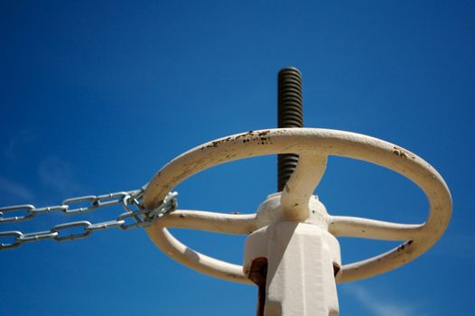 Industrial Valve & Chain Abainst A Deep Blue Sky.