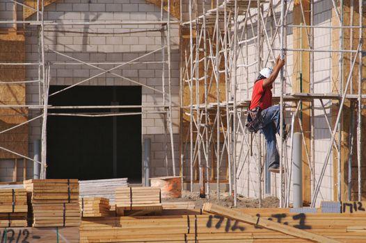 Carpenter climbing down scaffolding at a construction scene.