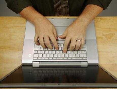 Man Using Laptop on Wooden Desk