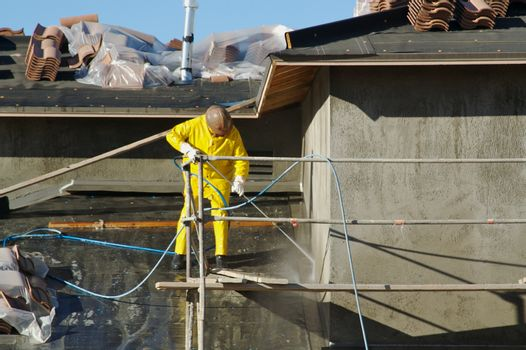 Construction worker pressure washes fresh applied surface of new home exterior.