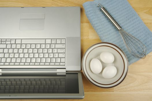 Laptop, eggs and mixer - online research for cooking and recipe information.