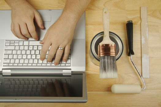 Handyman Researches on Laptop with paint brush, roller and wood stir stick by his side. Great image for online information regarding home improvement, additions and remodeling.