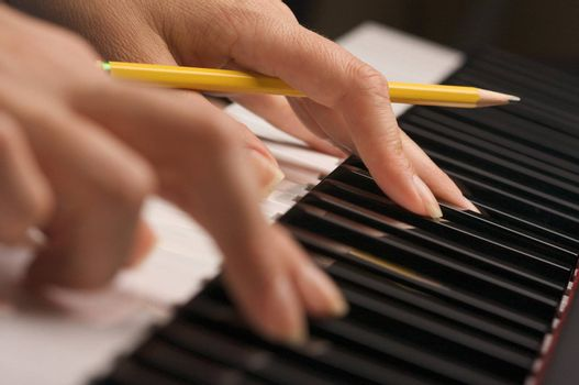 Woman's Fingers with Pencil on Digital Piano Keys