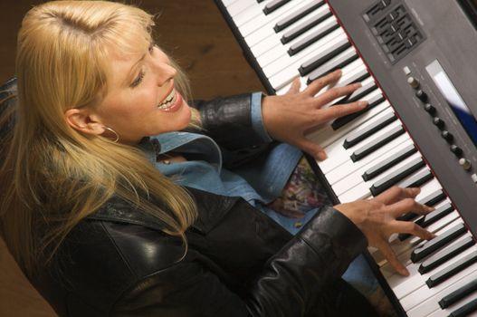 Femal Musician Sings While Playing Digital Piano