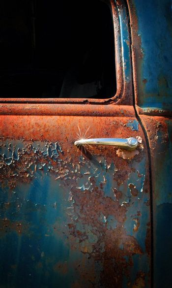 Close up of a door handle and sun burst on an old abandoned pick up truck with rust and blue weathered paint.