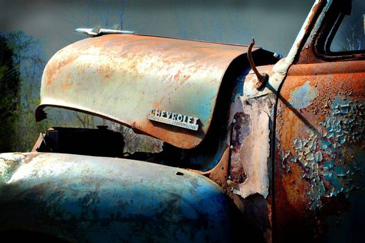 Partial view of the front end of an old abandoned Chevrolet Thriftmaster pickup truck with rust and weathered blue paint.