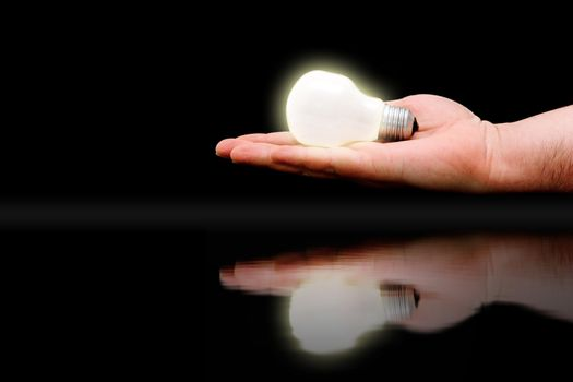 Concept : handing out bright ideas. Hand with lit bulb reflected on water surface