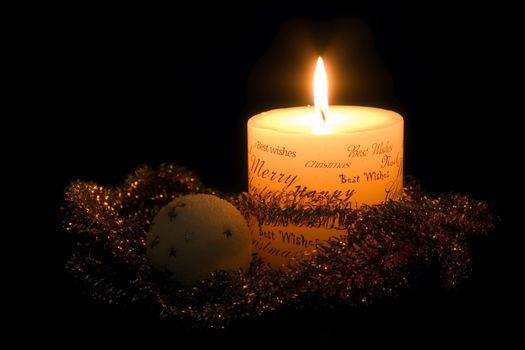 Lit white Christmas candle, golden ribbon and white christmas ball, on black background