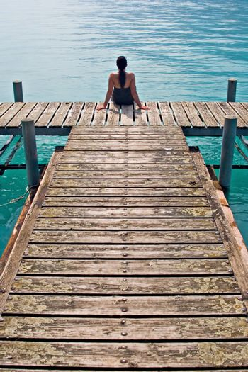 Woman contemplating in wooden dock