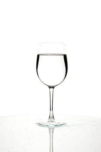 Glass of water with reflection on white background.