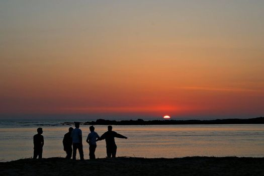 Group of friends playing at sunset.