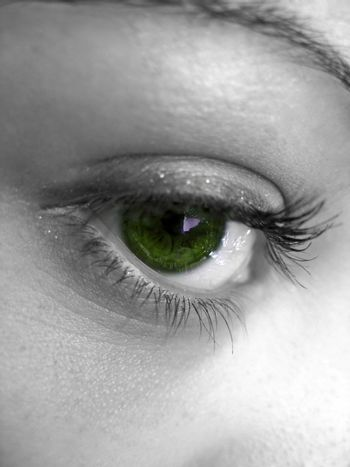 A macro shot of a pretty woman's green eye with selective color.