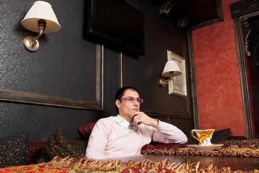 Successful young man sitting in luxury interior