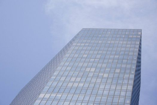An angled skyscraper building on a sunny blue day.