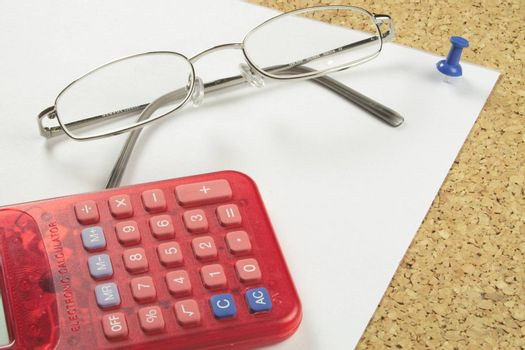 spectacles with a calculator on a piece of notepaper pinned to a board
