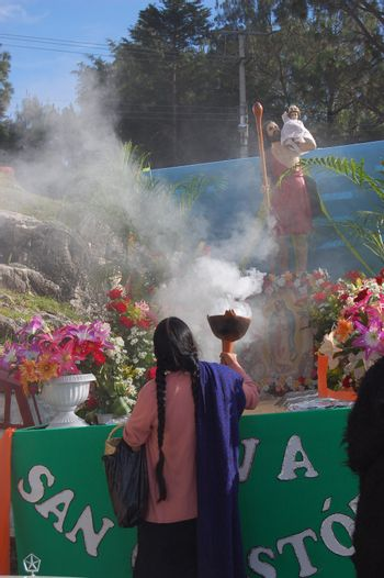 Mayan Indian woman offering incense to saint in Chiapas, Mexico
