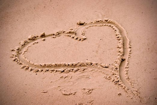 a love heart drawn in the sand at the beach