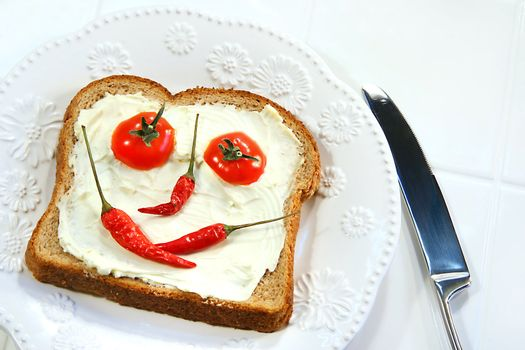Food arranged into a smiley face on sandwich