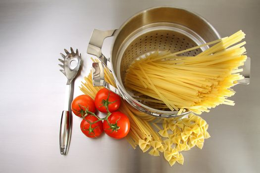 Overhead shot of pasta, tomatoes and pot on stainless steel
