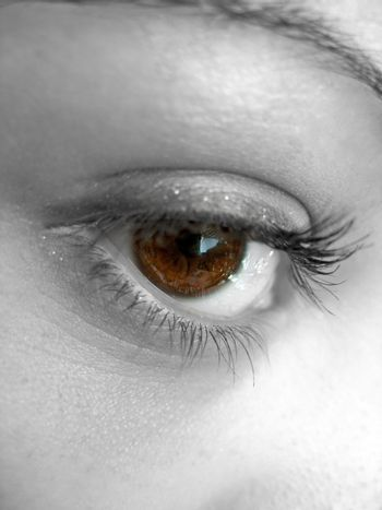 A macro shot of a pretty woman's brown eye with selective color.