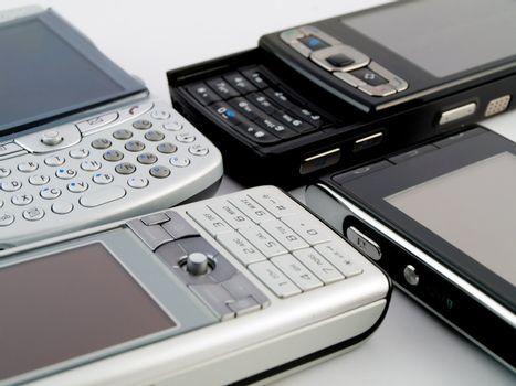 Stack Pile of Several Modern Mobile Phones PDA Cell Handheld Units Isolated on White Background