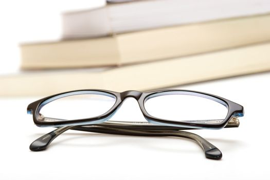 Books and reading glasses on white background