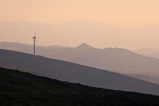Wind turbine working on hill top at sunset
