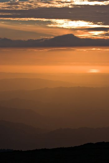 View over layered mountains on a beautiful Sunset.