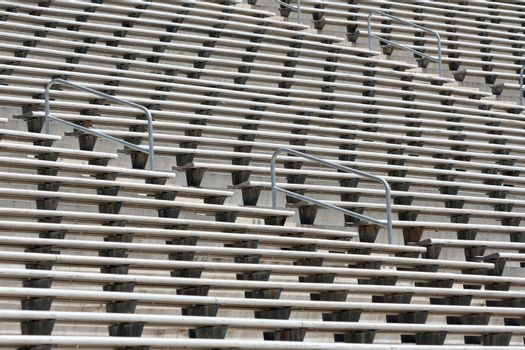 Rows of empty metal football stadium bleachers