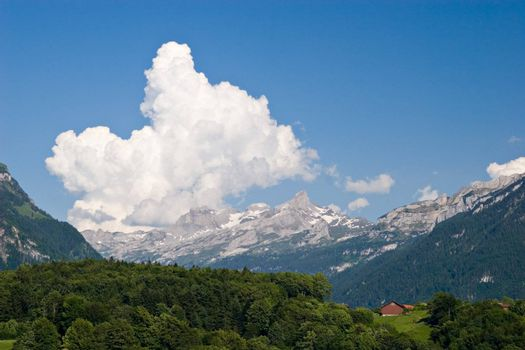 Swiss spring landscape. Fields, woods, mountains and blue sky with big white cloud