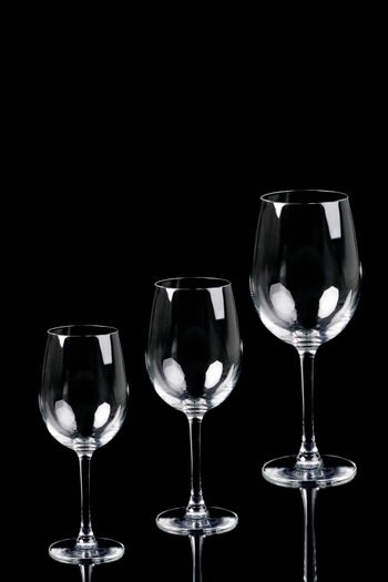 Three empty glasses over black background with reflection. Water, white wine and red wine.