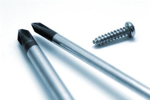 Screw and screwdrivers on white background