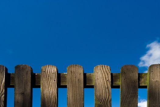 Wood fence against deep blue sky