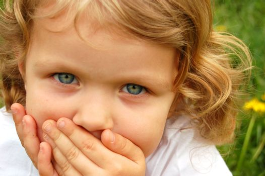 portrait of small pretty girl with curly hair and blue eyes