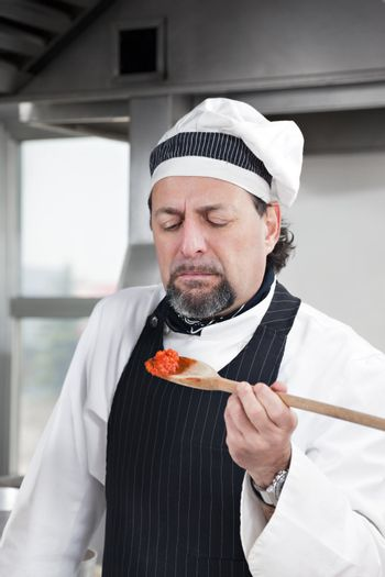 mature chef holding wooden spool and tasting tomato sauce.
