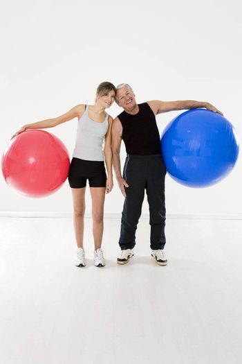 senior adult and daughter exercising with fitness ball in gym