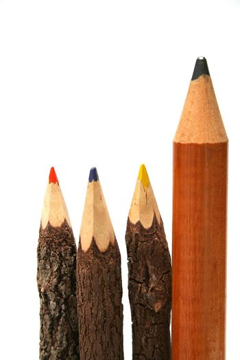 Three unusual pencils made of natural wood and one simple huge pencil vertical