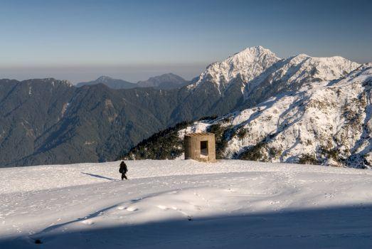 Man walk and blockhouse stand on snow white mountain.