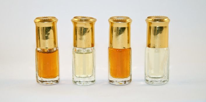 four small bottles of perfume on a white background