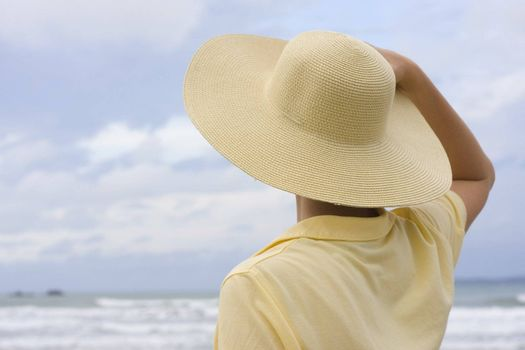 Woman with yellow hat and shirt on a beach
