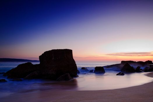Landscape picture of rocks on the beach at sunset