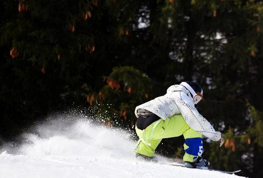 A snowboarder lands a jump as snow flies behind him