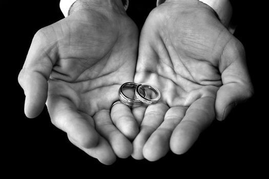 This is a close up on the groom's hands. He is holding his and her wedding rings. The image is black and white
